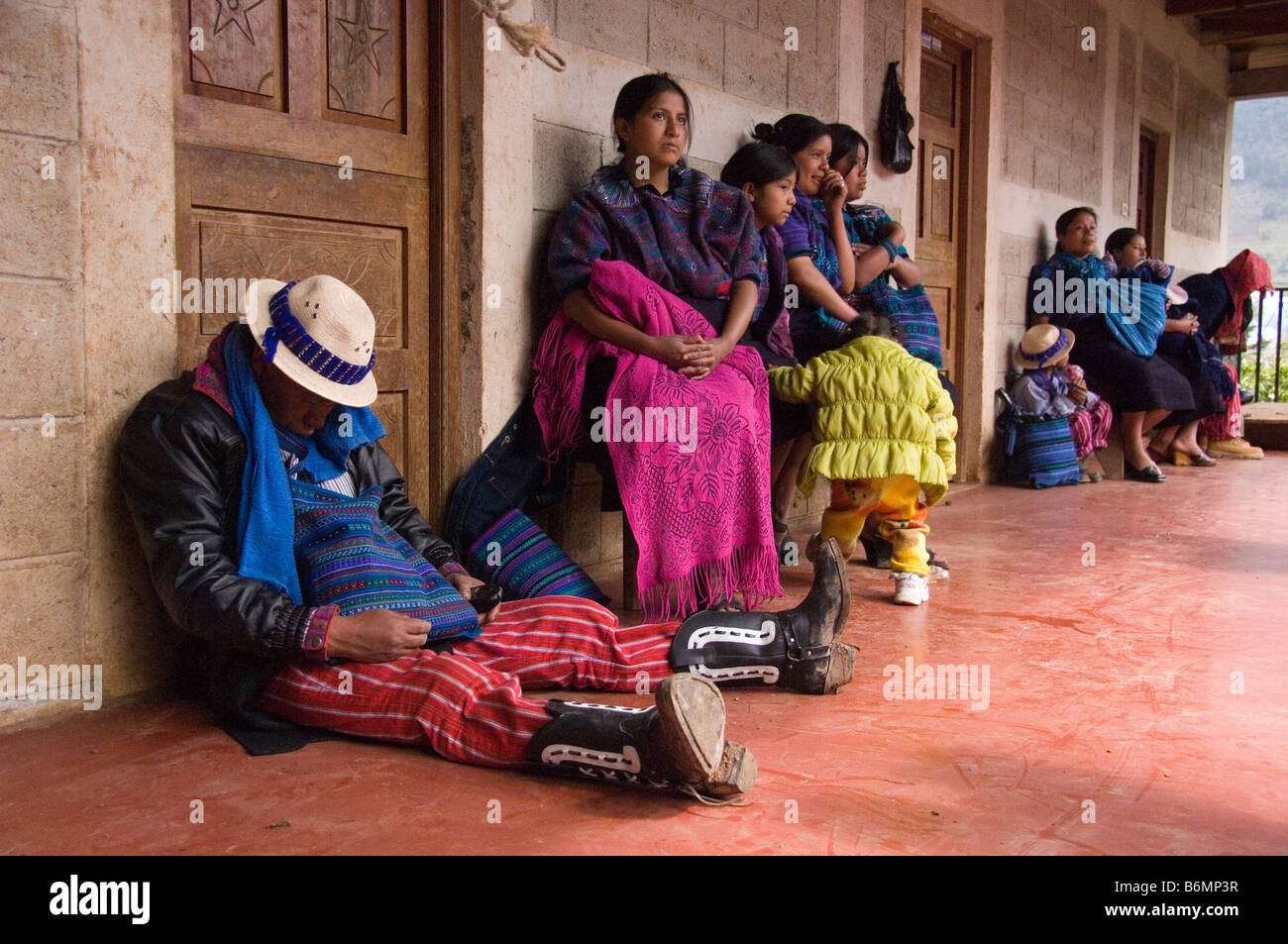 Boozer leans against a wall in front of his female family members.Annual festival(Oct 31-Nov 2)Todos Santos Cuchumatan,Guatemala - Stock Image