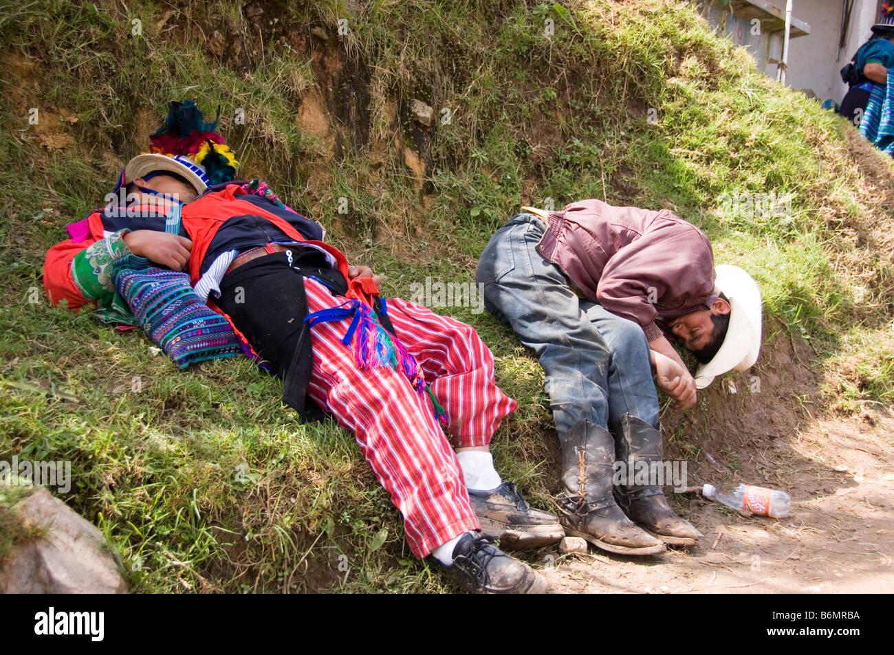 Two drunken men sleeping beside the road during the annual festival (Oct 31-Nov 2) .Todos Santos Cuchumatan,Guatemala - Stock Image