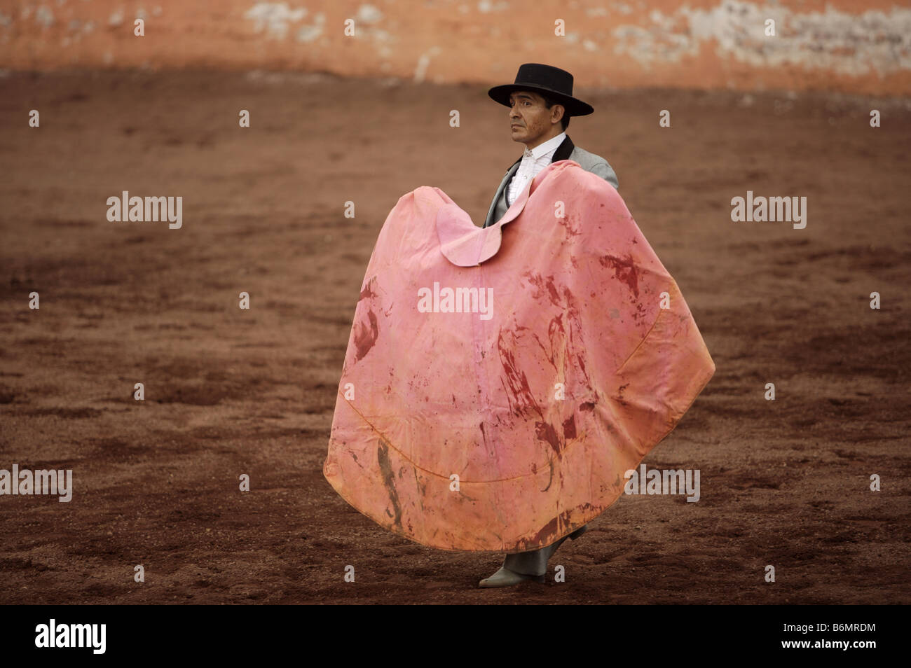 eccc1206993 A bullfighter holds a cape splattered with blood as he waits for a bull to  charge