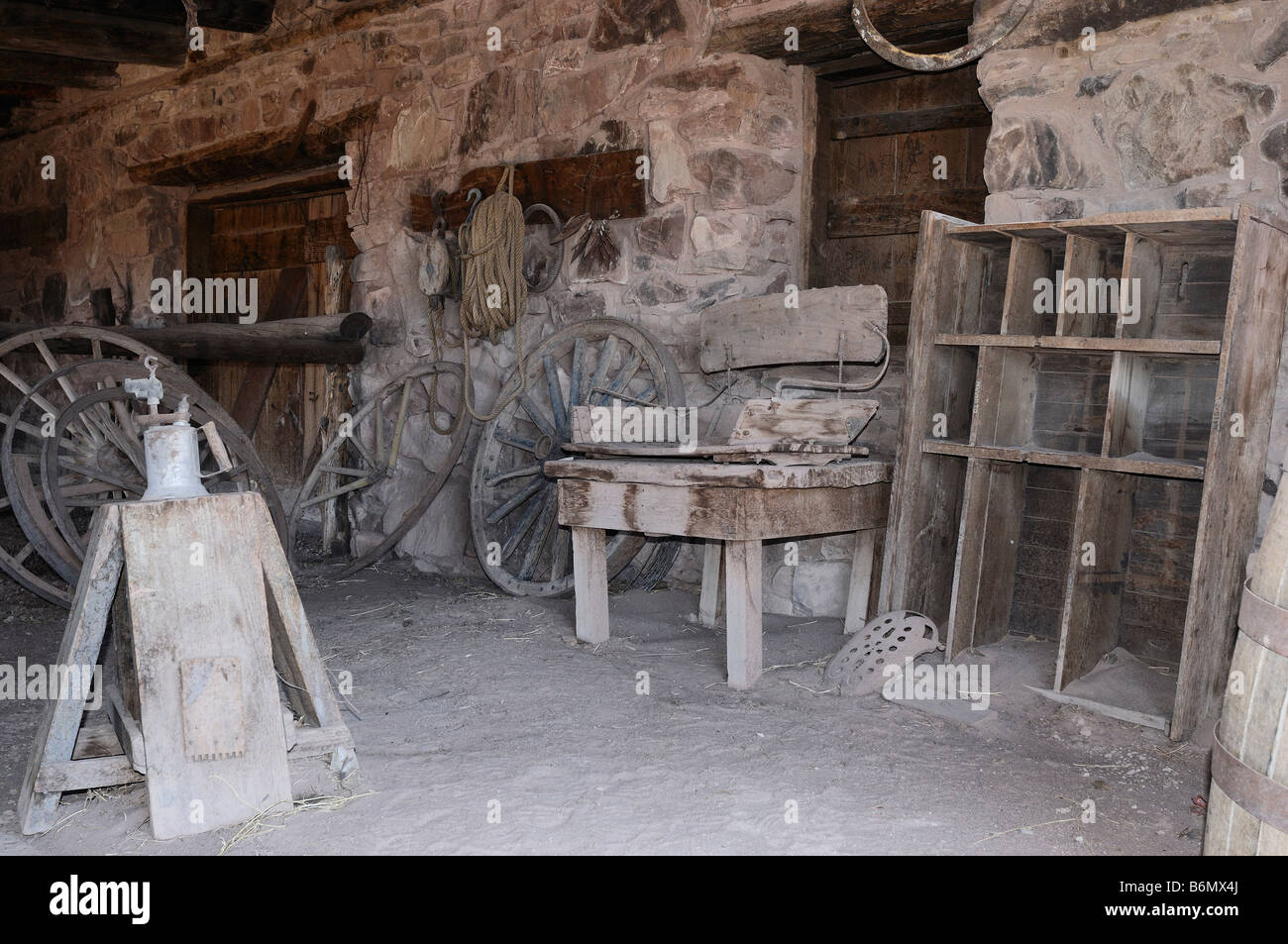 Interior view of the stables at the Hubbell Trading Post in Ganado, Arizona with wagon wheels and other historical - Stock Image