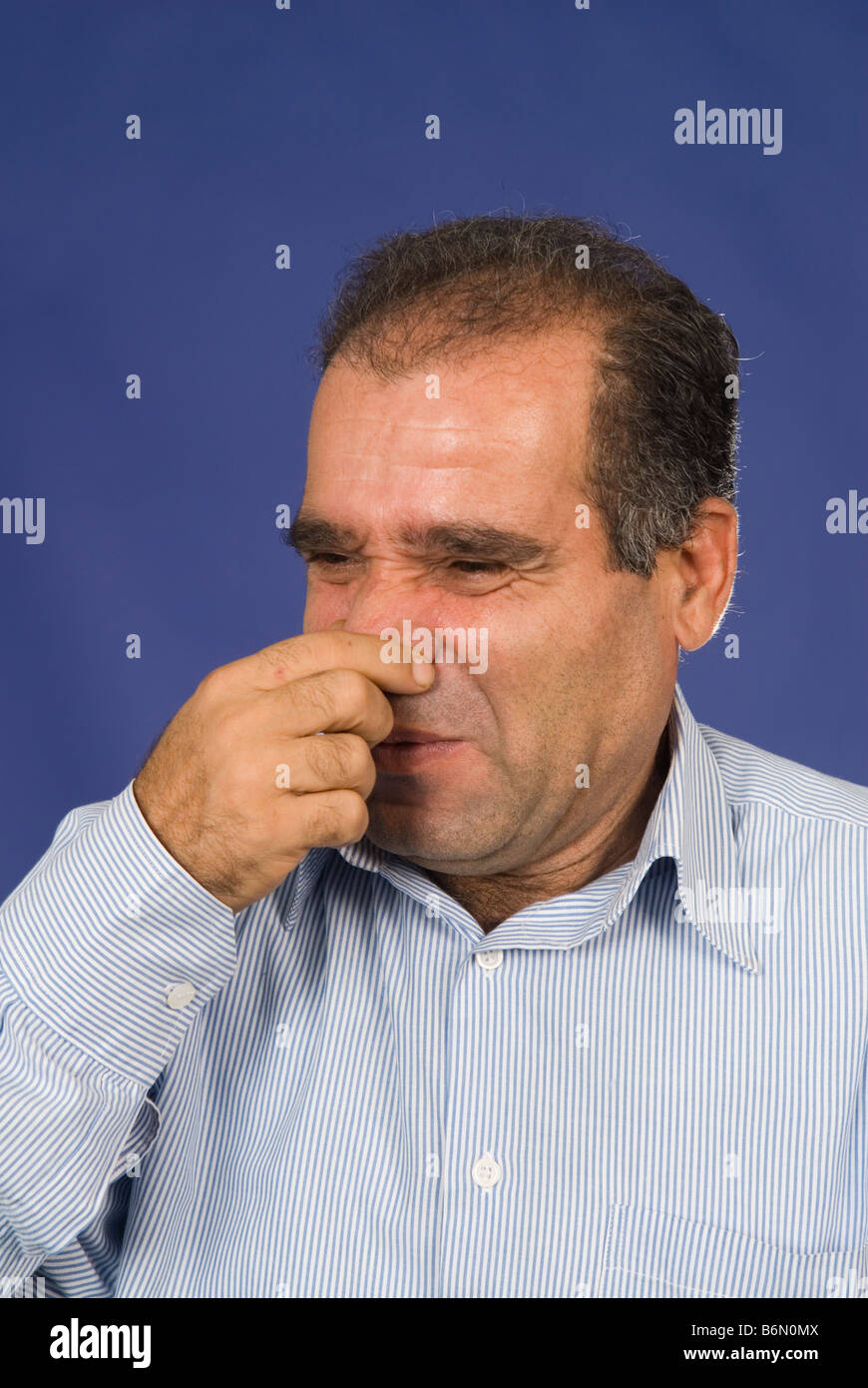 Man holding his nose to avoid bad smell - Stock Image
