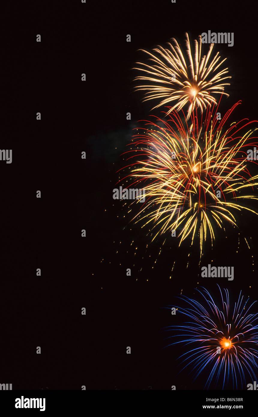 Large aerial fireworks fill black sky - Stock Image
