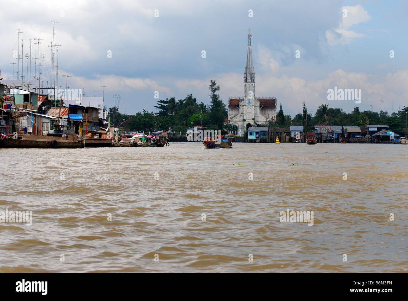 The river, catholic Church and town of Cai Be, Mekong Delta, Vietnam - Stock Image