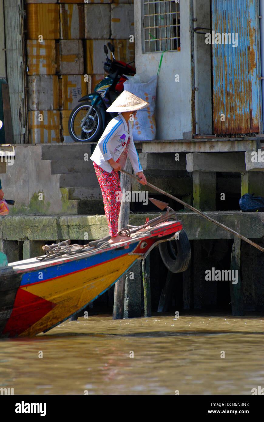 Vietnamese boatwoman skulling from sampan, town of Cai Be, Mekong Delta, Vietnam - Stock Image