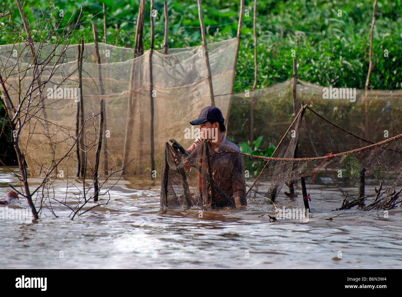 Fisherman with nets and the banks of Tien Giang River, Mekong Delta, Vietnam - Stock Image