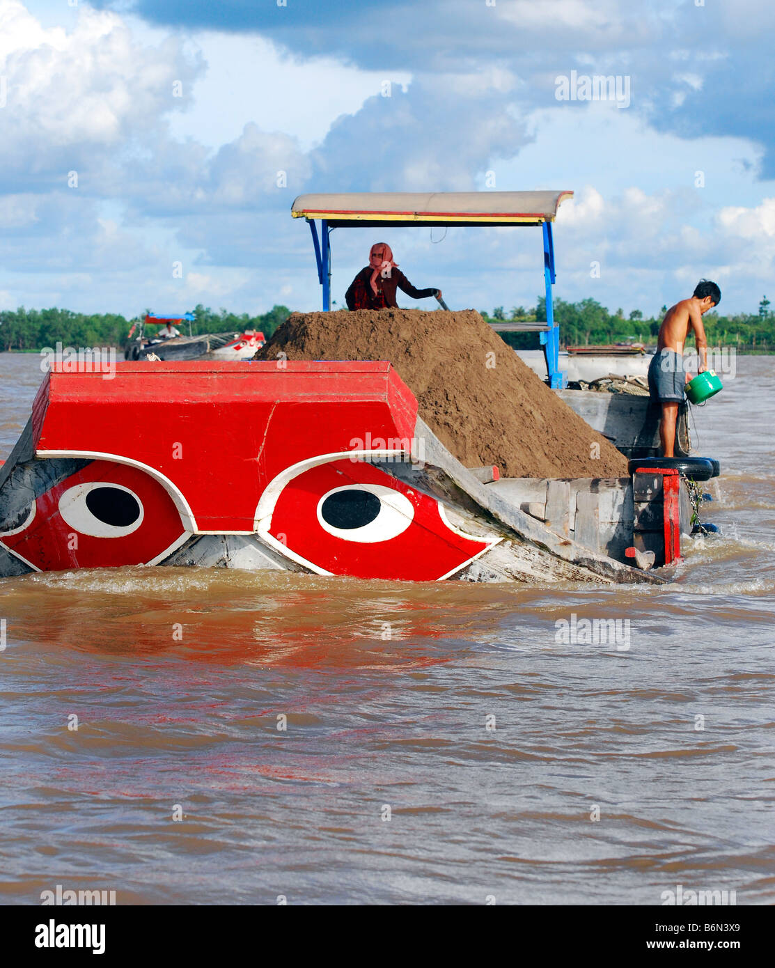 Brightly coloured red river boat carrying topsoil,  Tien Giang River, Mekong Delta, Vietnam - Stock Image