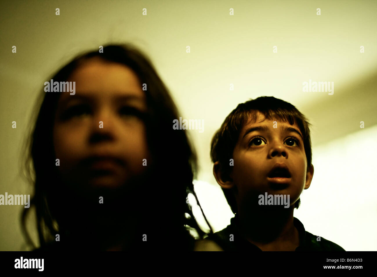 Girl aged five and boy seven watch television. - Stock Image