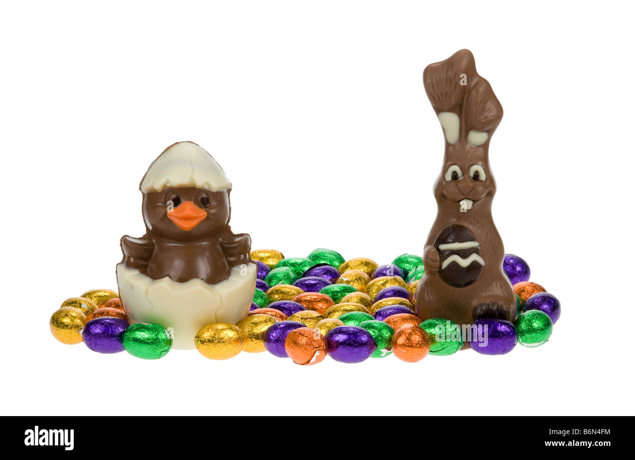 cute easter bunny and chick surrounded by chocolate easter eggs isolated on a white background - Stock Image