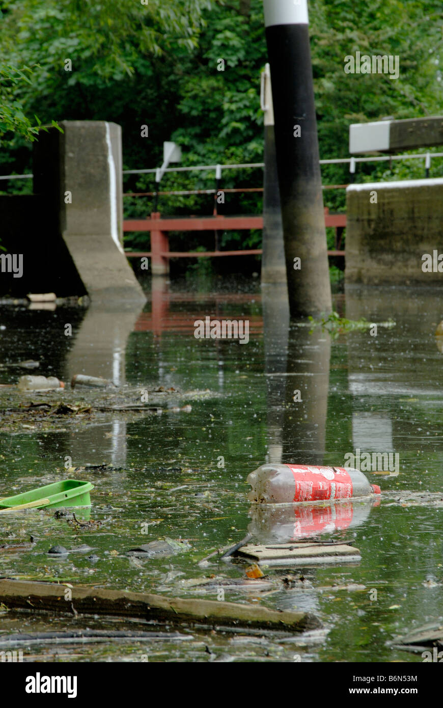 River pollution: plastic bottles, tubs, wood and deadfall floating on surface of River Wey with lock gates behind, - Stock Image