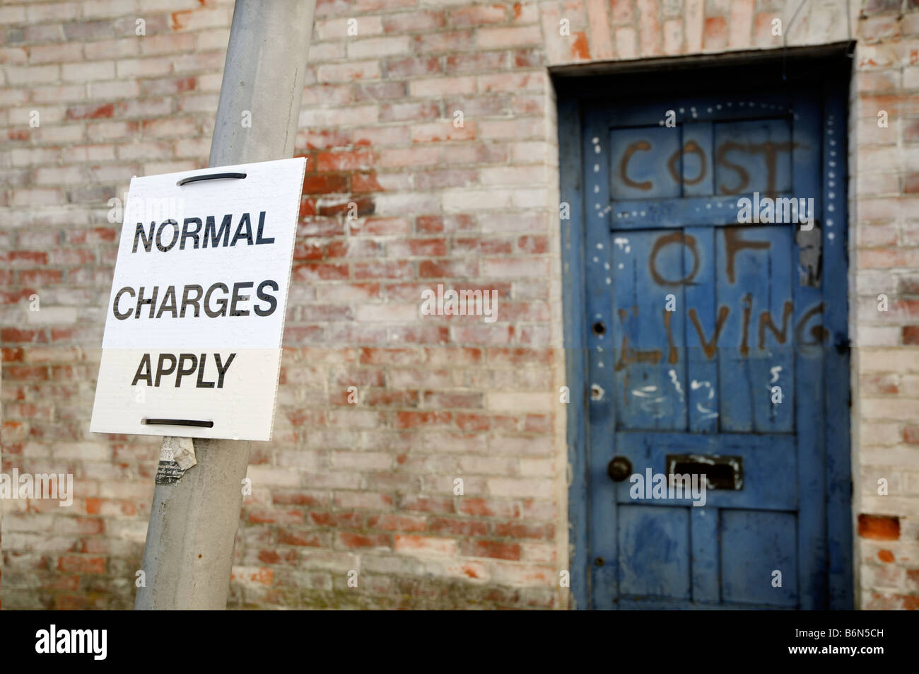 A sign regarding parking charges is attached to a post in front of a door bearing the graffited words 'Cost - Stock Image