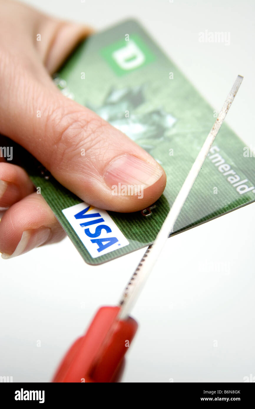 Concept of hand holding a visa credit card while scissors cuts it up symbolizing lean times - Stock Image