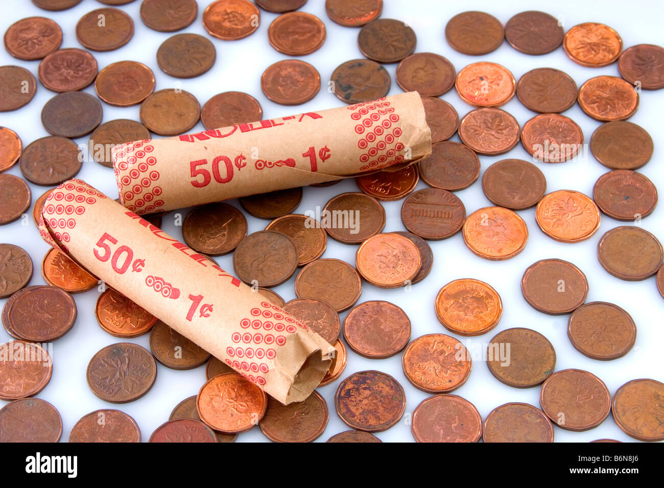 Concept of paper coin rollers amoung pennies on white background symbolizing lean times - Stock Image