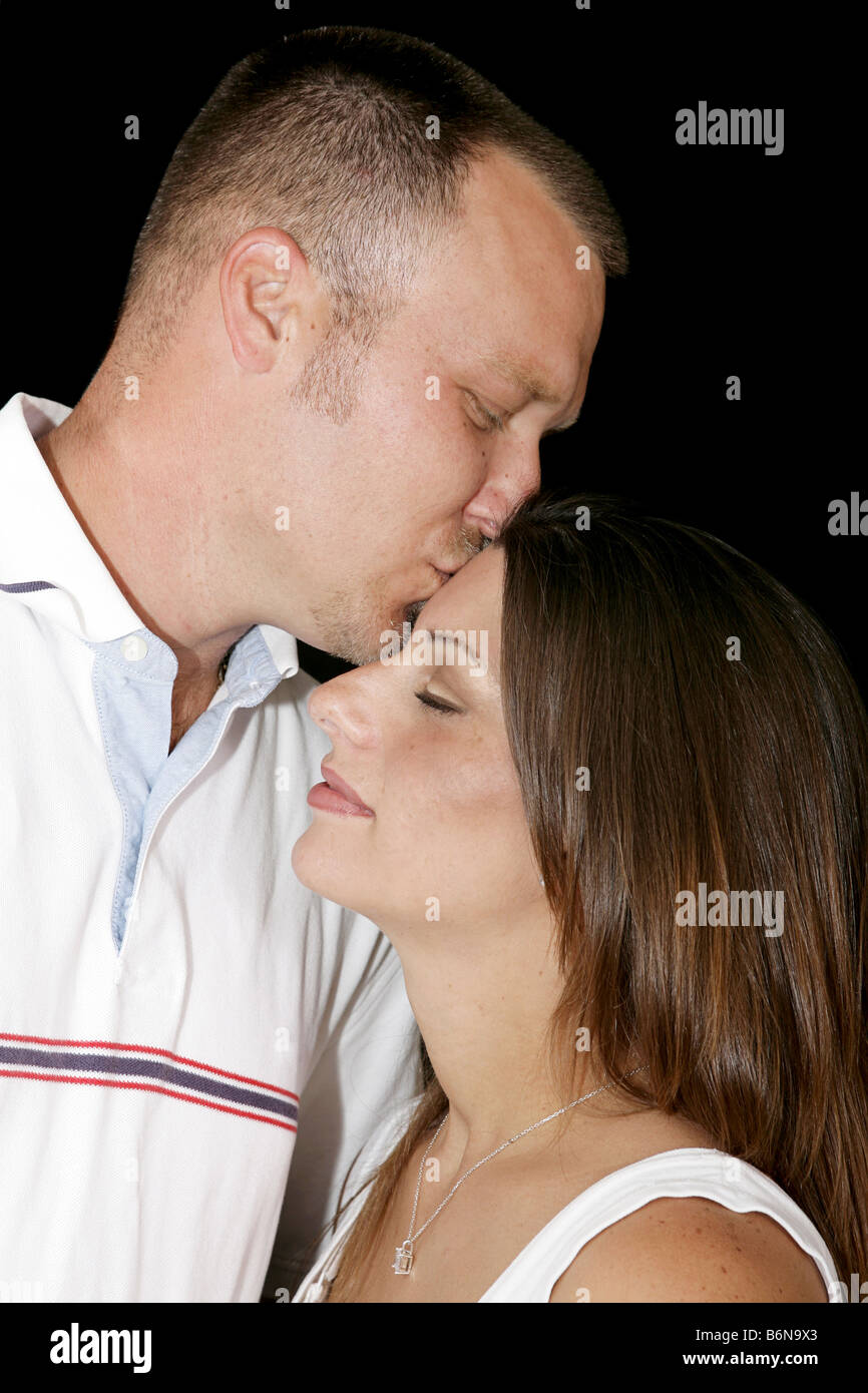 Intimate portrait of a young couple in love He is kissing her tenderly on the forehead - Stock Image