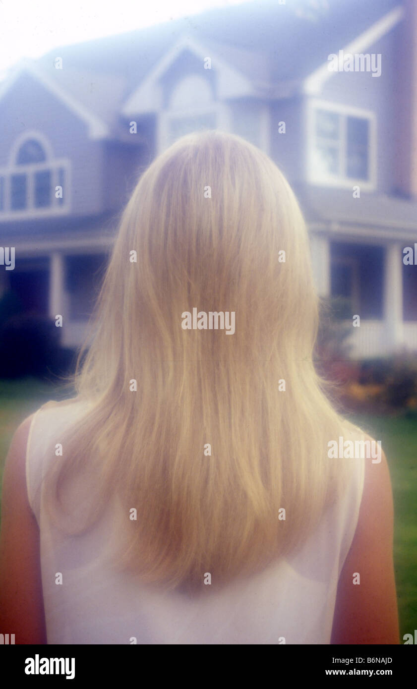 blond woman from behind with house in background - Stock Image