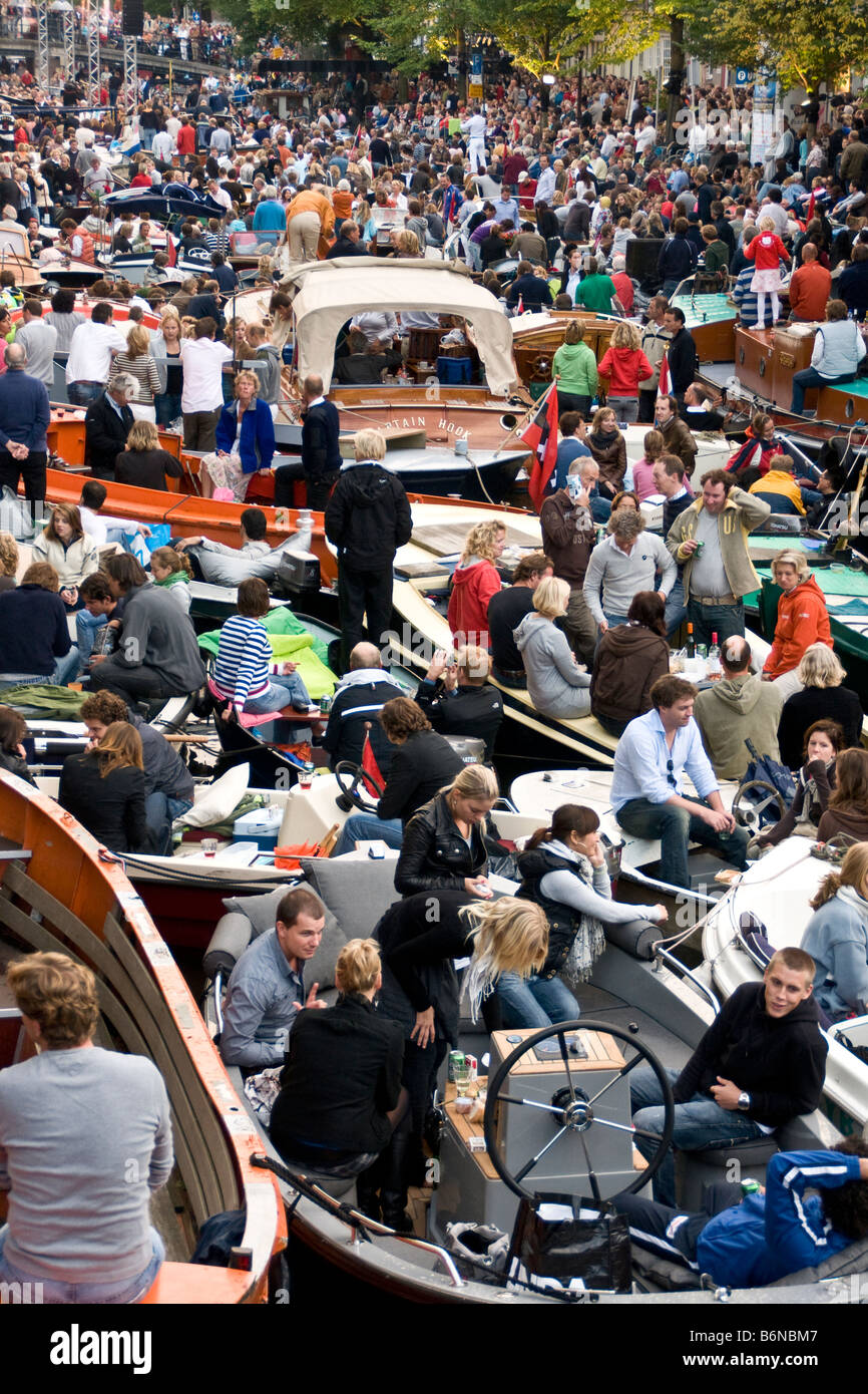 Amsterdam crowd in boats at free open air summer festival of classical music concerts on Prinsengracht Canal Stock Photo