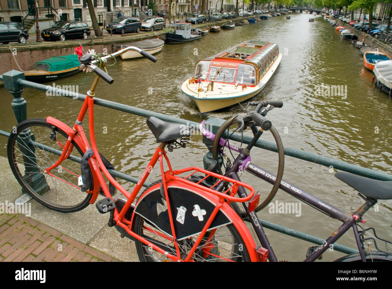 Amsterdam bikes locked to bridge with sightseeing cruise boat in Prinsengracht canal - Stock Image