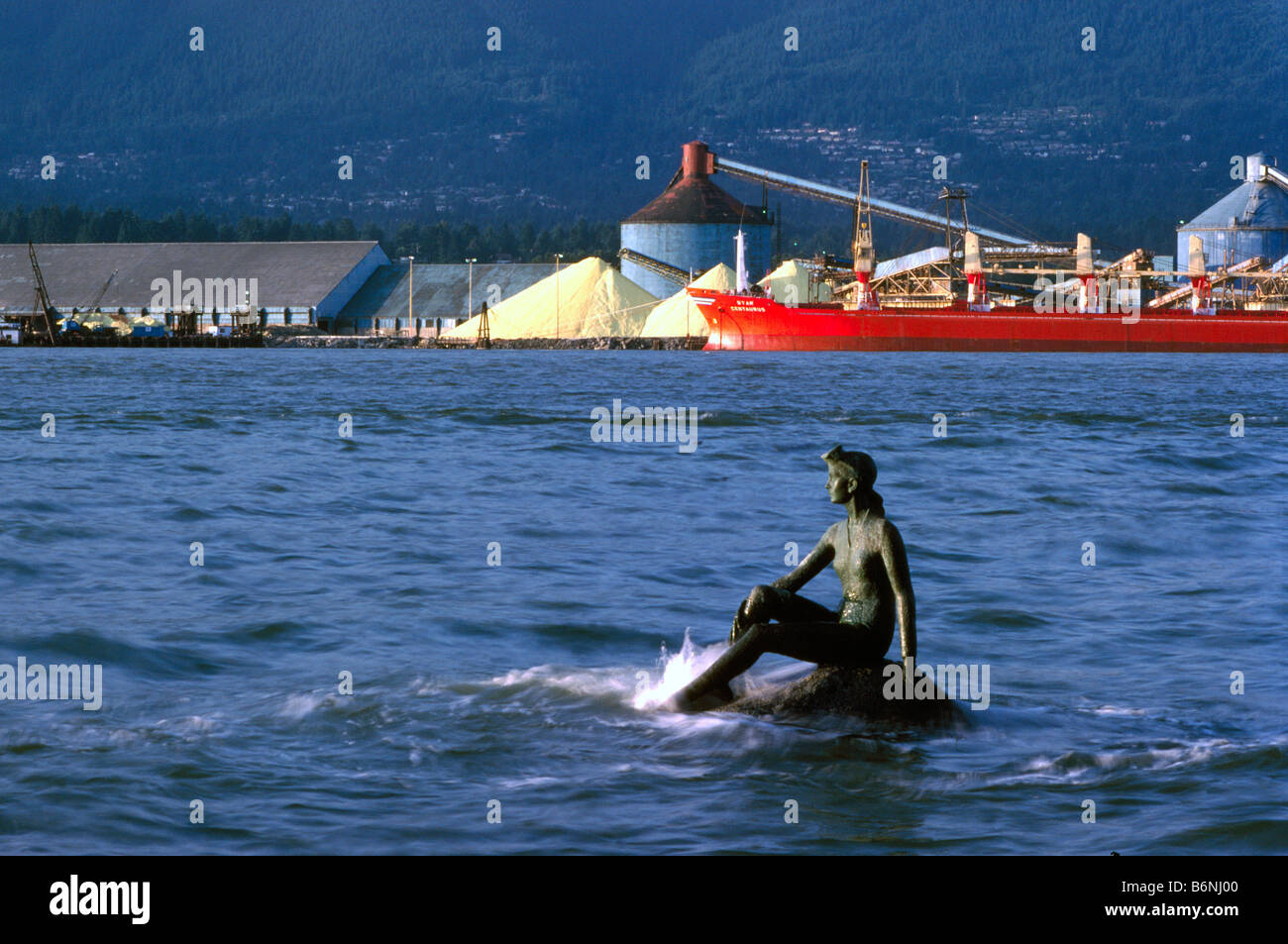Girl in a Wetsuit Sculpture in Stanley Park and Freighter loading Sulphur in North Vancouver British Columbia Canada - Stock Image