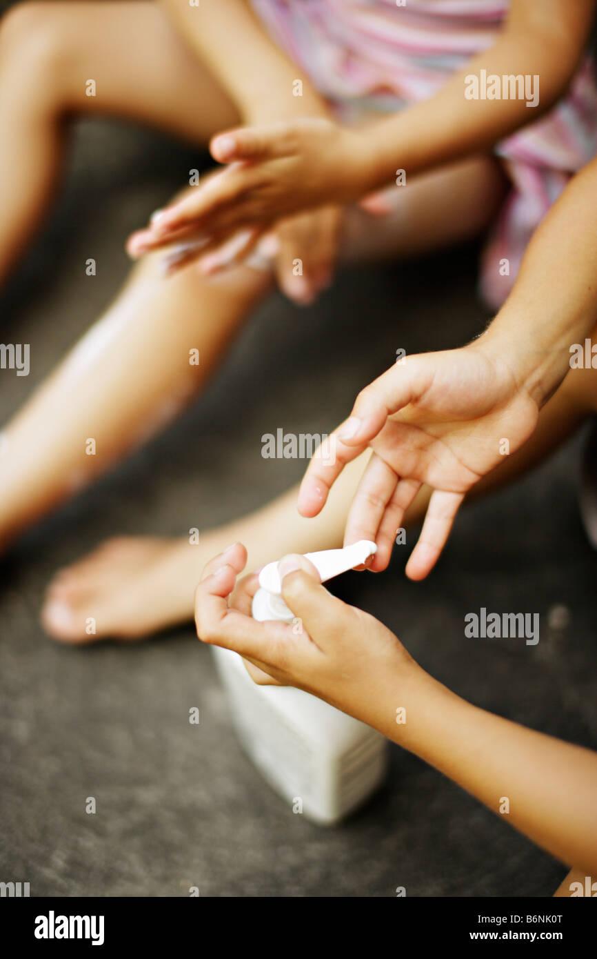 Children apply suncream boy aged six girl aged five - Stock Image