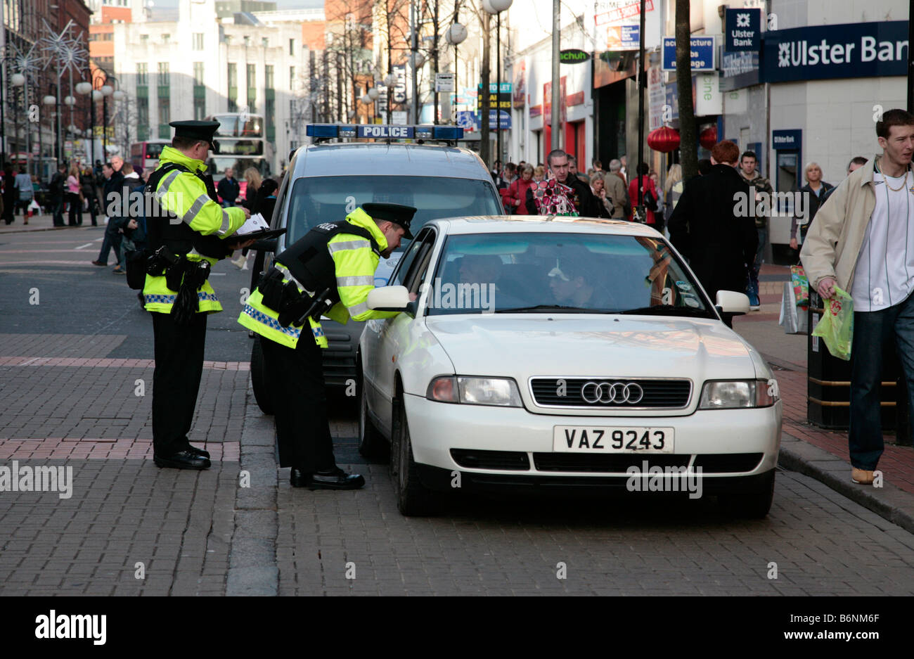 police question a driver of an audi car in a routine check in a pedestrian area of belfast city centre uk - Stock Image