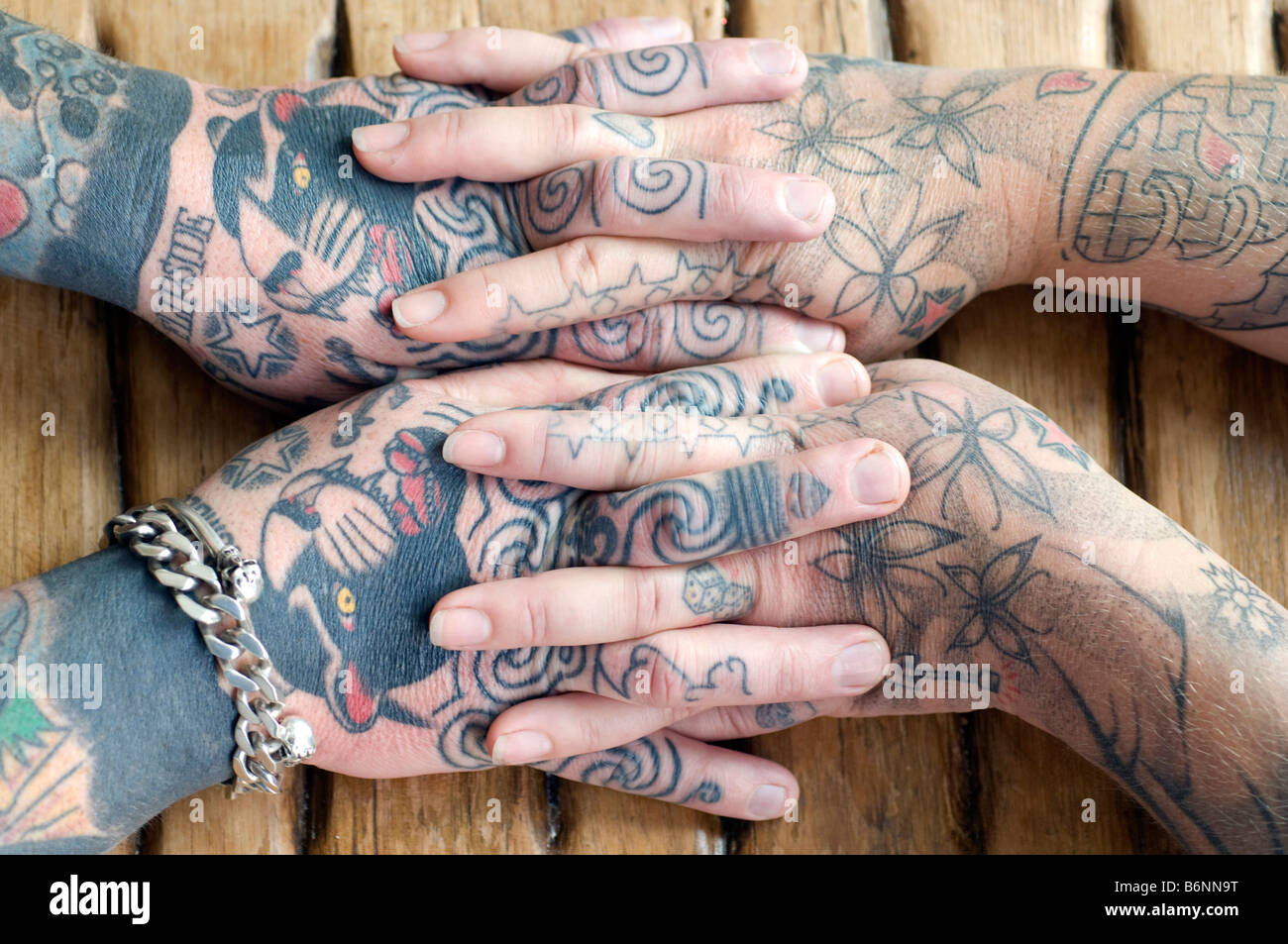 The entwined hands of a married couple who both have extensive tattoos - Stock Image
