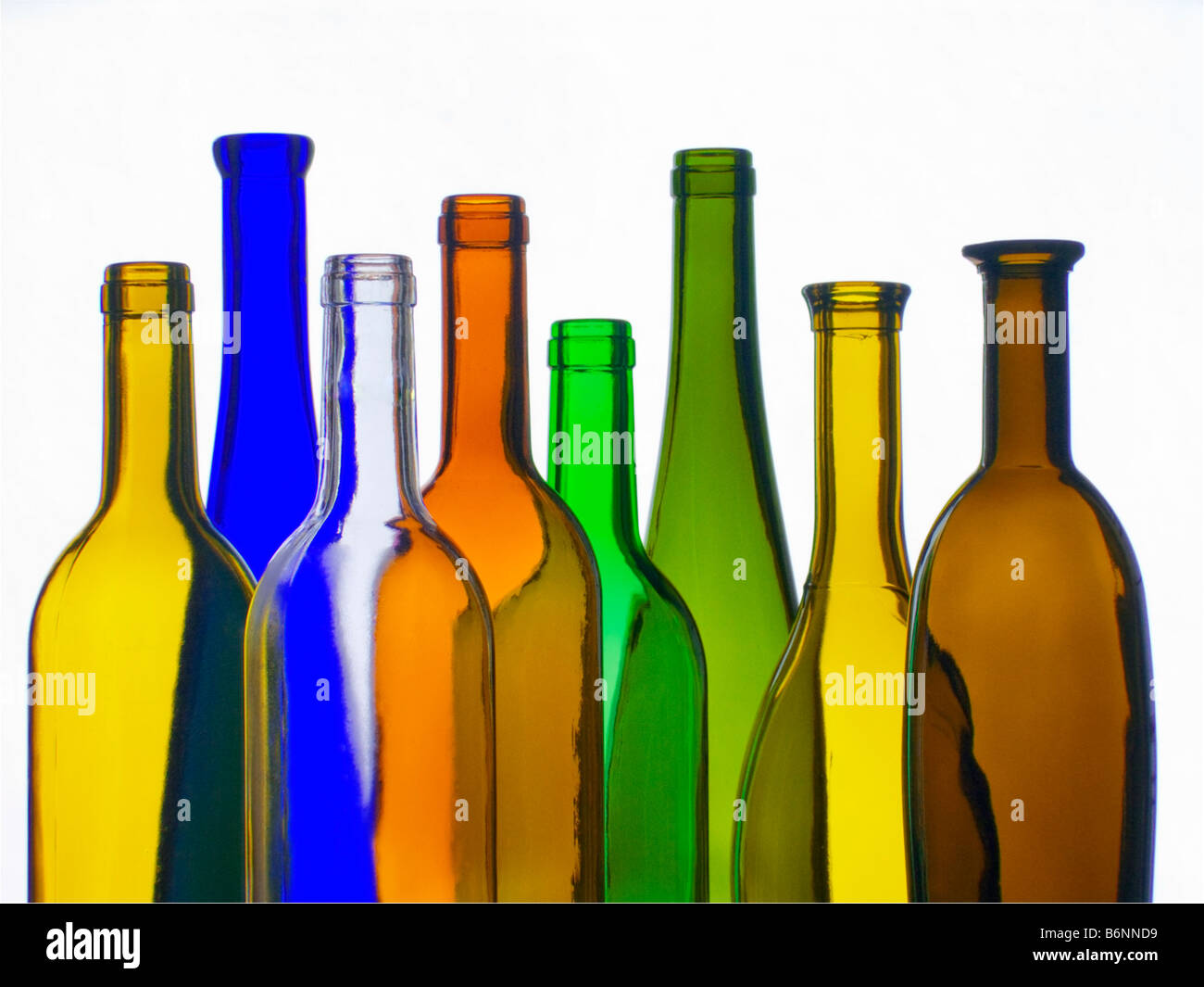 Selection of different colourful empty wine bottles in front of a white wall  background Stock Photo