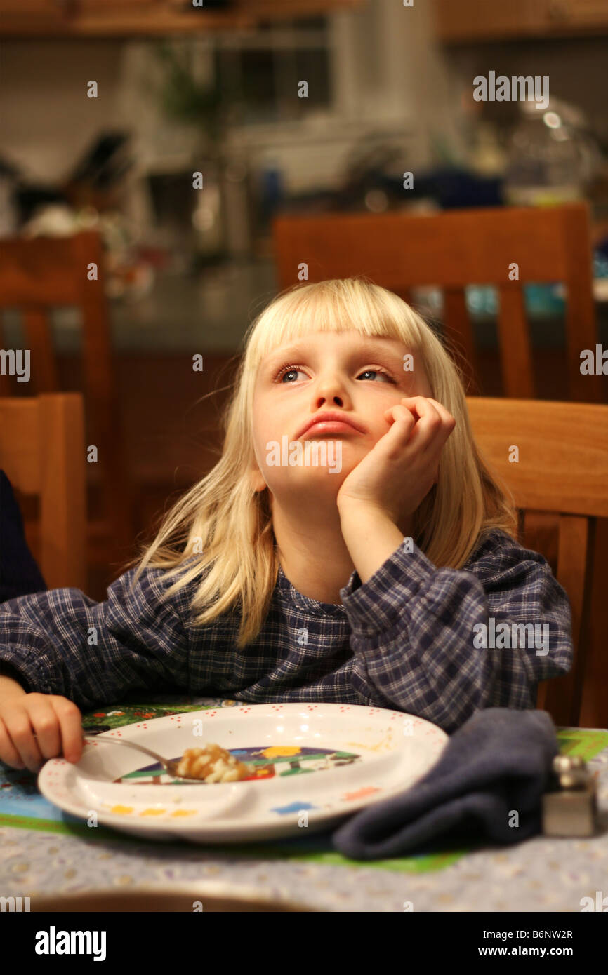 A sad five year old blonde girl looking up has one last bite of dinner to eat - Stock Image