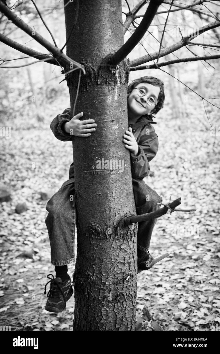 black & white image of young boy climbing a tree smiling at the camera in smug self-satisfction - Stock Image