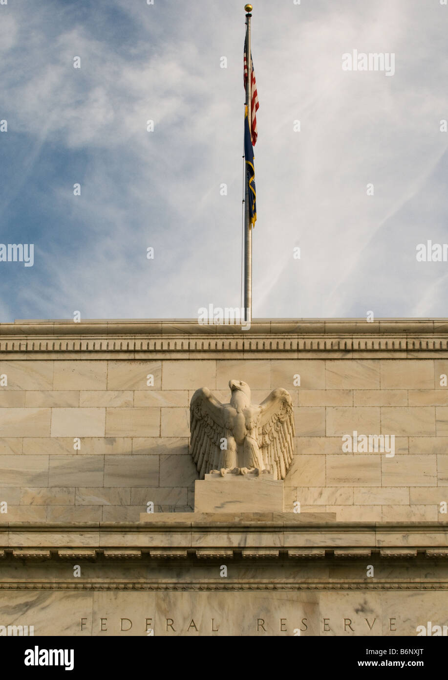 US flag atop the Federal Reserve Building, Washington DC (detail) with American flag - Stock Image
