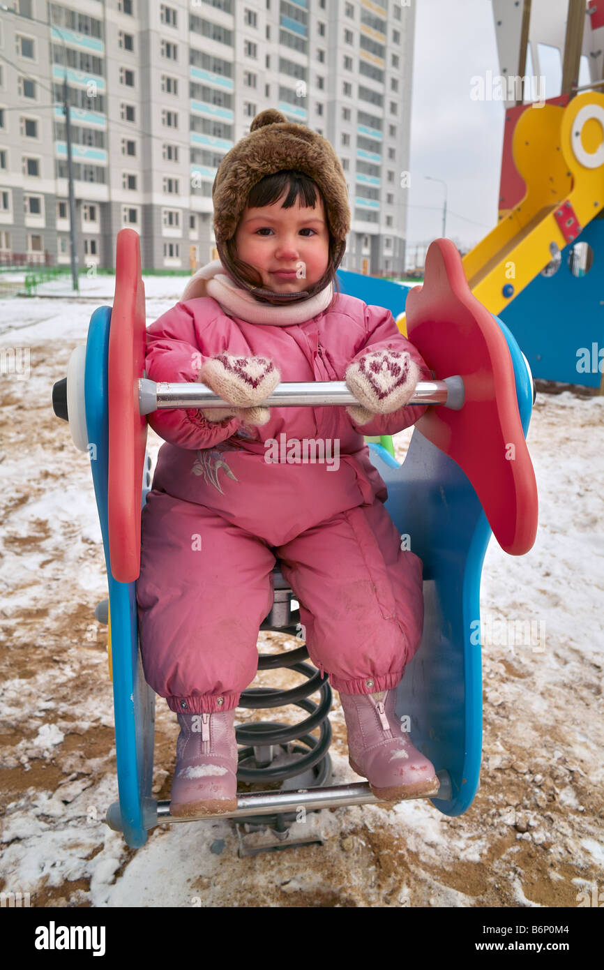 Little girl plays outdoor and pose for photograph dingle dangle on spring teeterboard - Stock Image