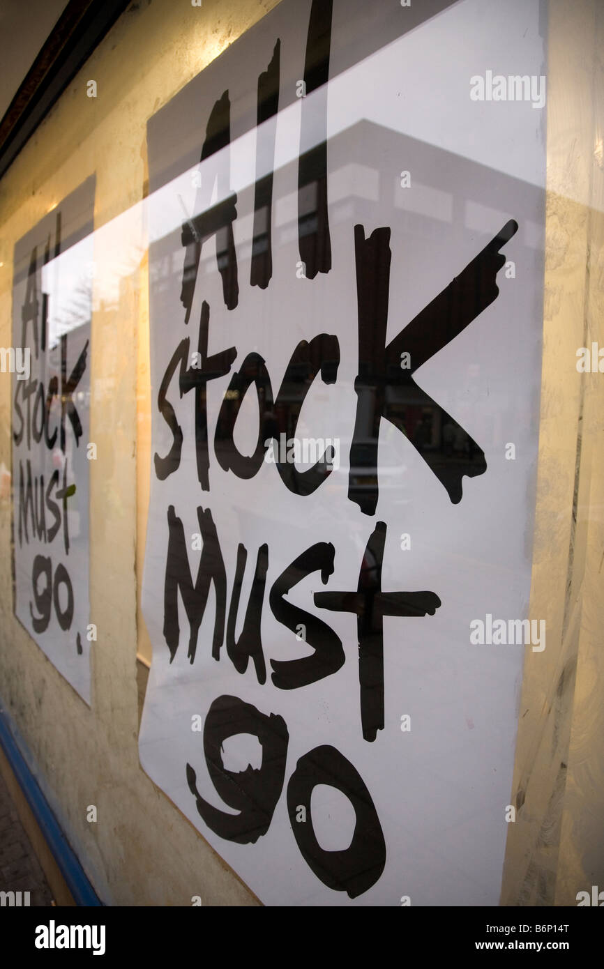 Posters in a shop window announce that 'all stock must go'. - Stock Image