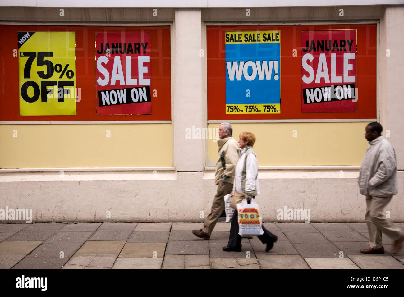 Signs announce the start of the January sales. Shoppers pass by the window. Stock Photo