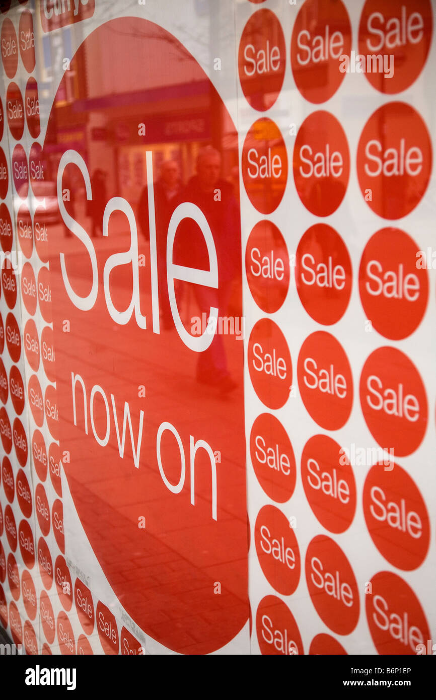 A sign in a shop window announces the start of the January sales. - Stock Image