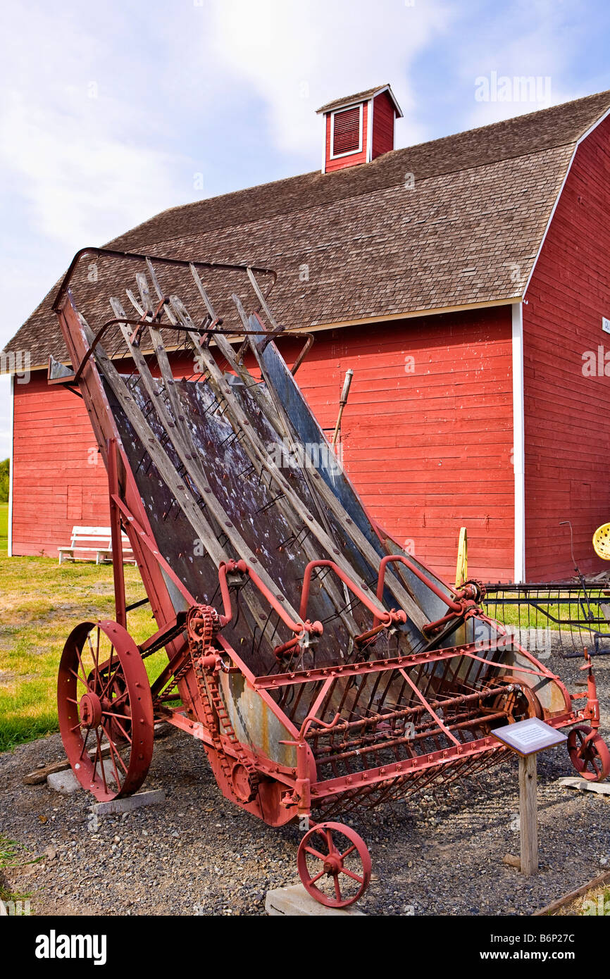 image of an antique horse drawn hay loader with a big red barn in