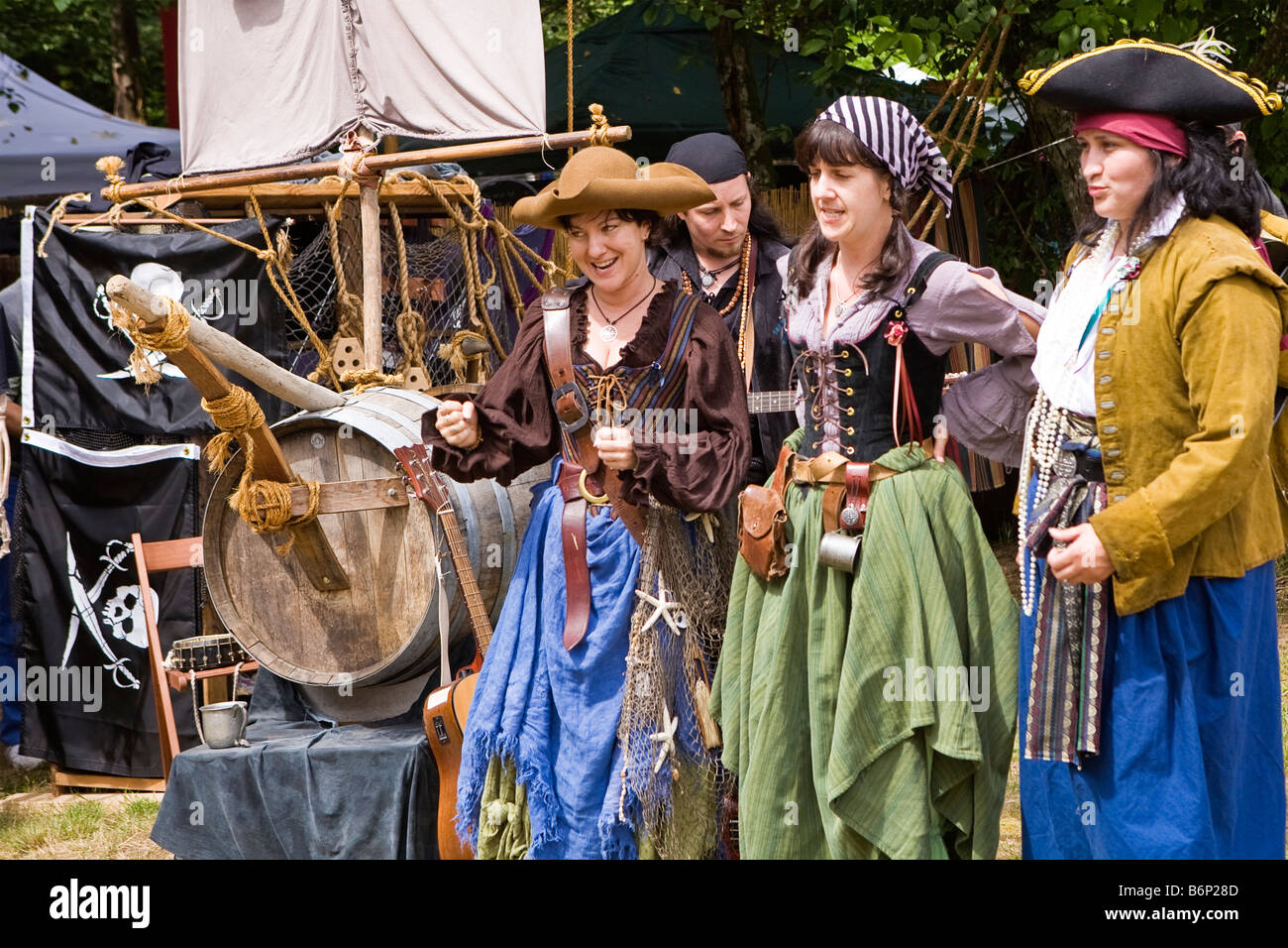 Image of a group of women all dressed in pirate costumes singing and playing instruments at a Renaissance Fair - Stock Image