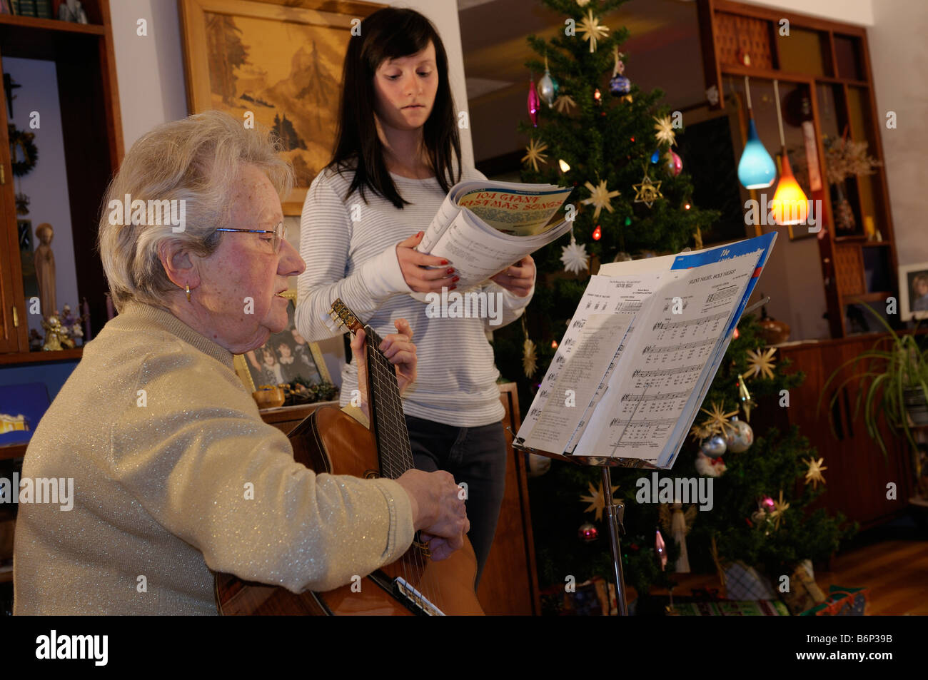 Grandmother with guitar and teenage granddaughter singing Christmas carols at home by the decorated tree Stock Photo