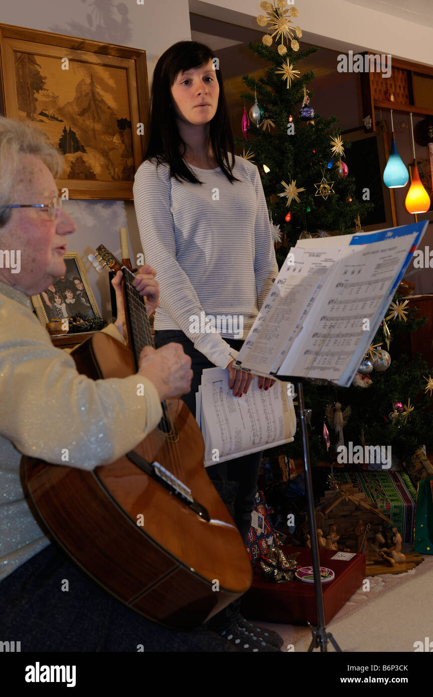Grandmother playing guitar and teenage granddaughter singing Christmas carols indoors at home by the decorated tree Stock Photo