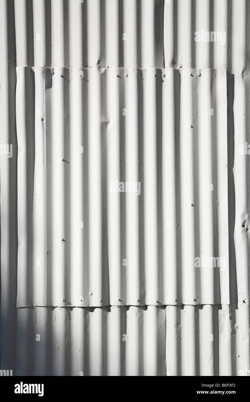 A detail of white painted corrugated sheet metal on the outside of a building in Carpinteria California. - Stock Image