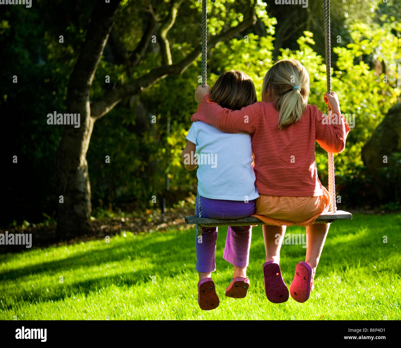 Two girls, 3-6 years, swinging in a verdant back yard. - Stock Image