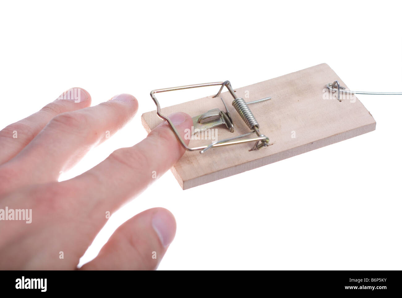 Mans hand catched in mousetrap over white - Stock Image