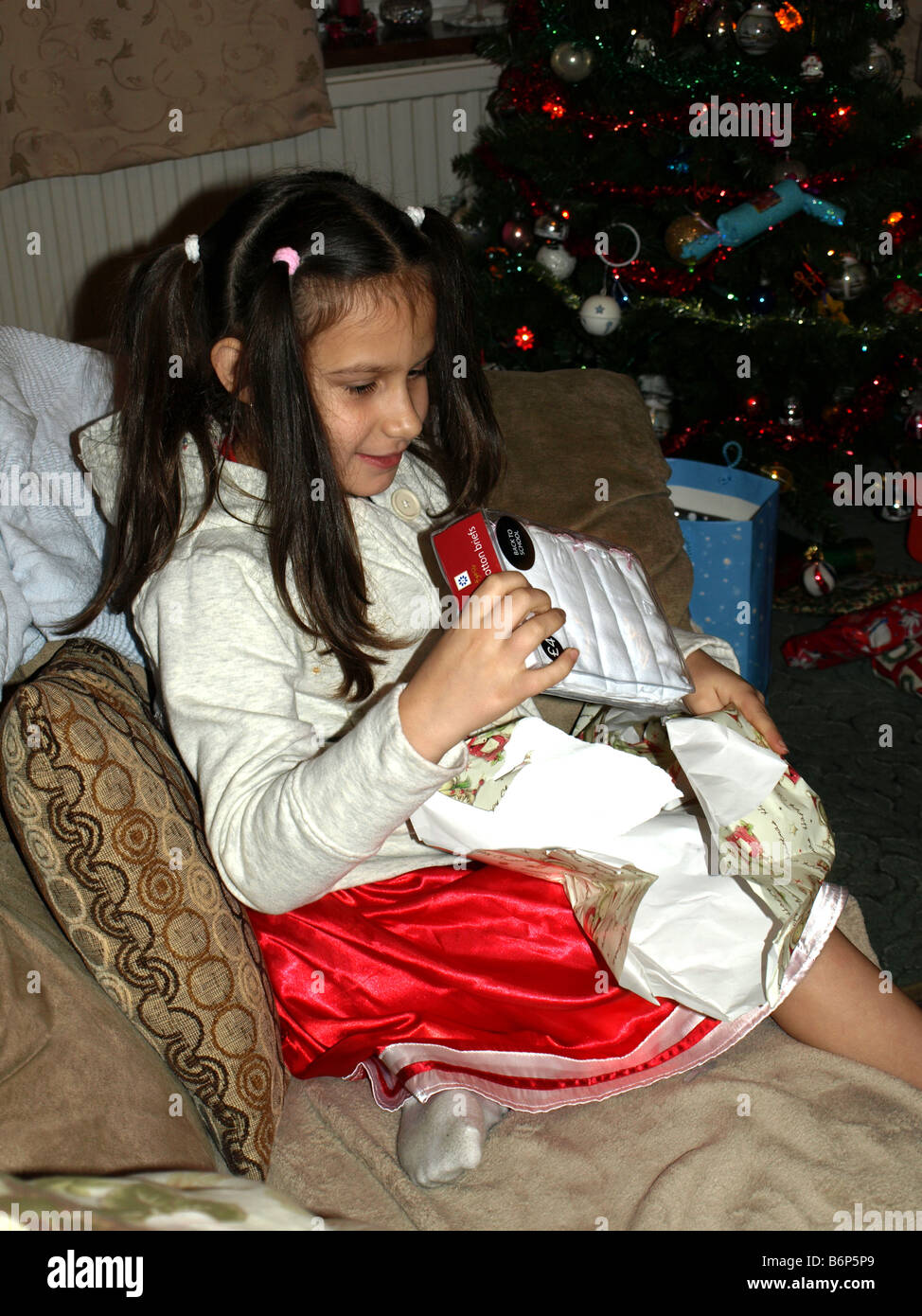 An 8 year old girl opening a Christmas present Stock Photo: 21385793 ...