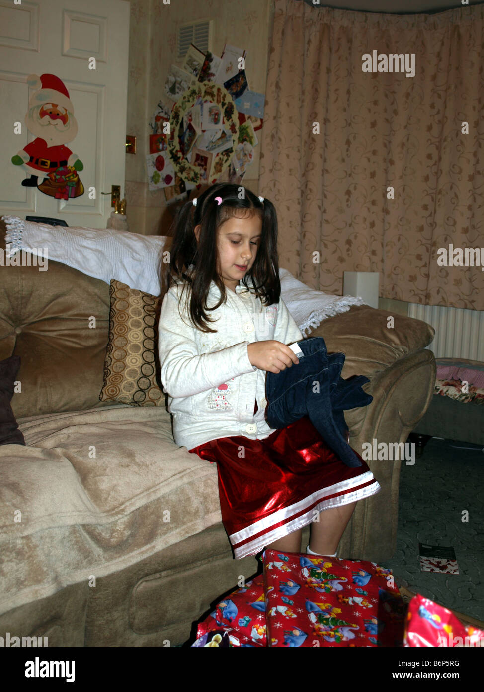 An 8 year old girl opening presents on Christmas morning Stock Photo ...