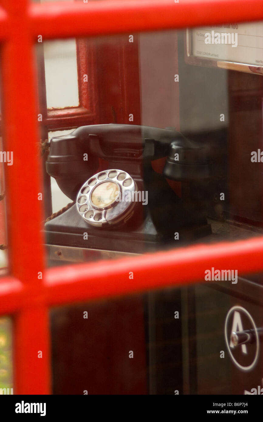 Old telephone though the window of a Telephone box - Stock Image