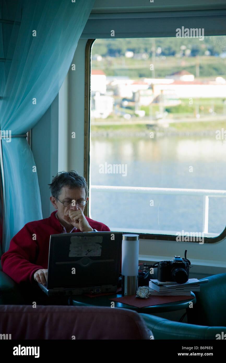 Simon Calder writing notes on his laptop board Akademik Sergey Vavilov Ushuaia harbor harbour Tierra del Fuego Argentina - Stock Image