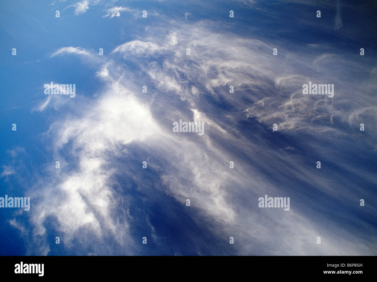 Dramatic wispy white clouds against a blue sky - Stock Image