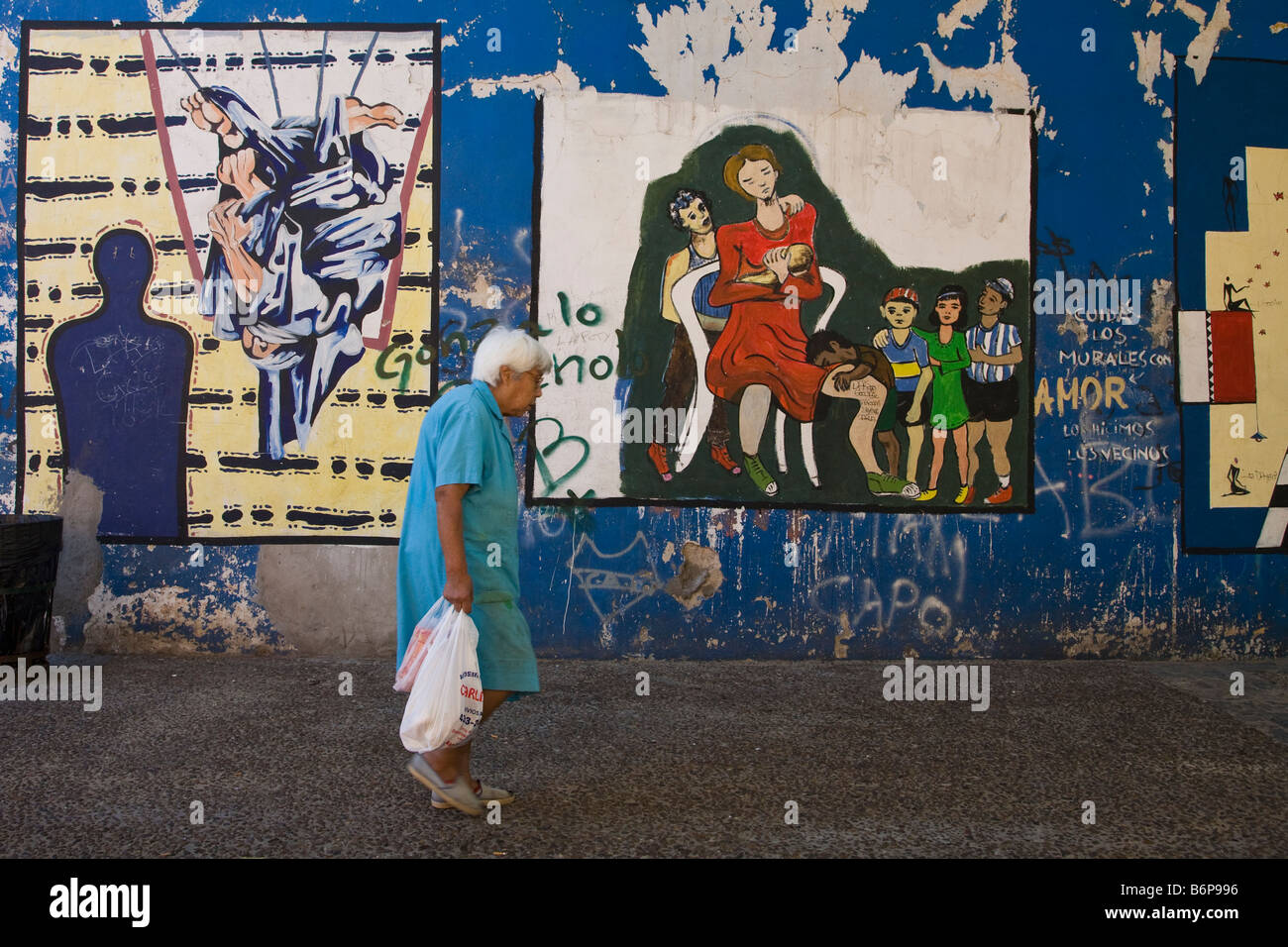 Old lady with shopping bags passes street art in La Boca Buenos Aires Argentina South America - Stock Image