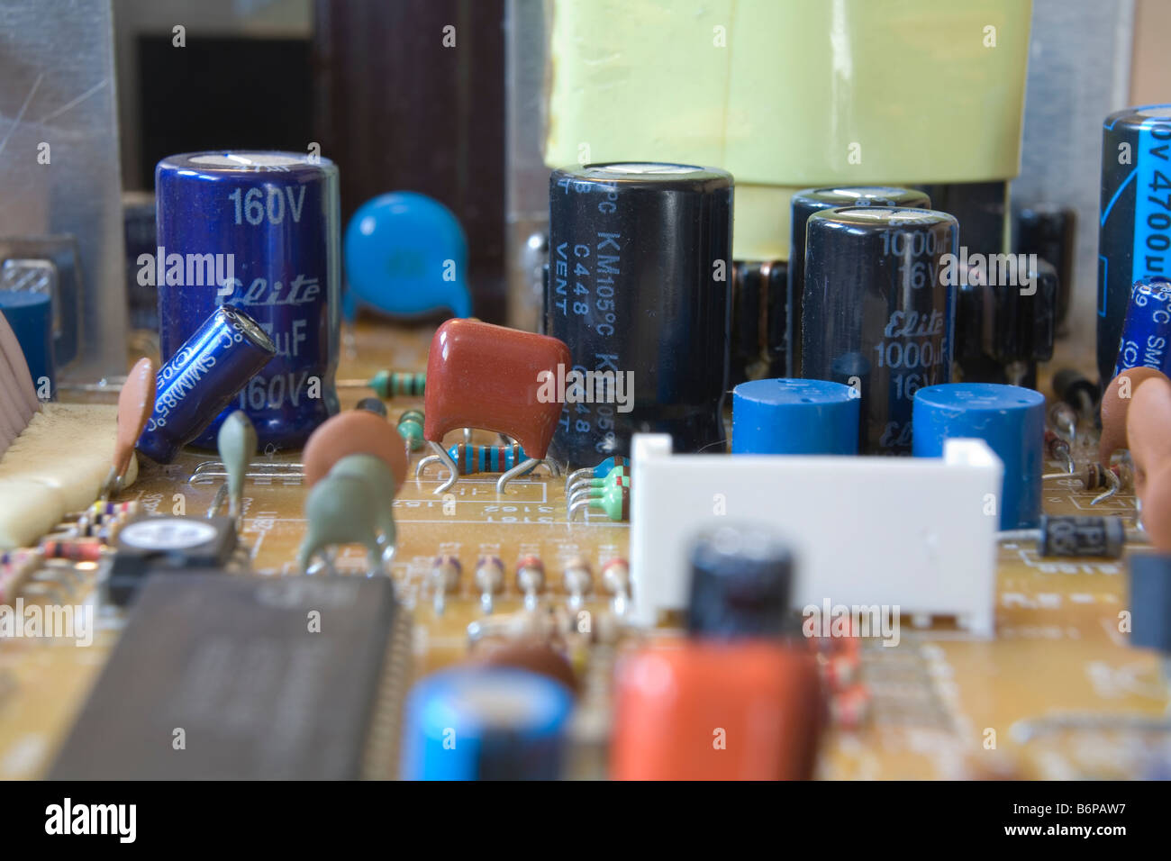 Electrolytic capacitors standing tall on an electronic circuit board - Stock Image