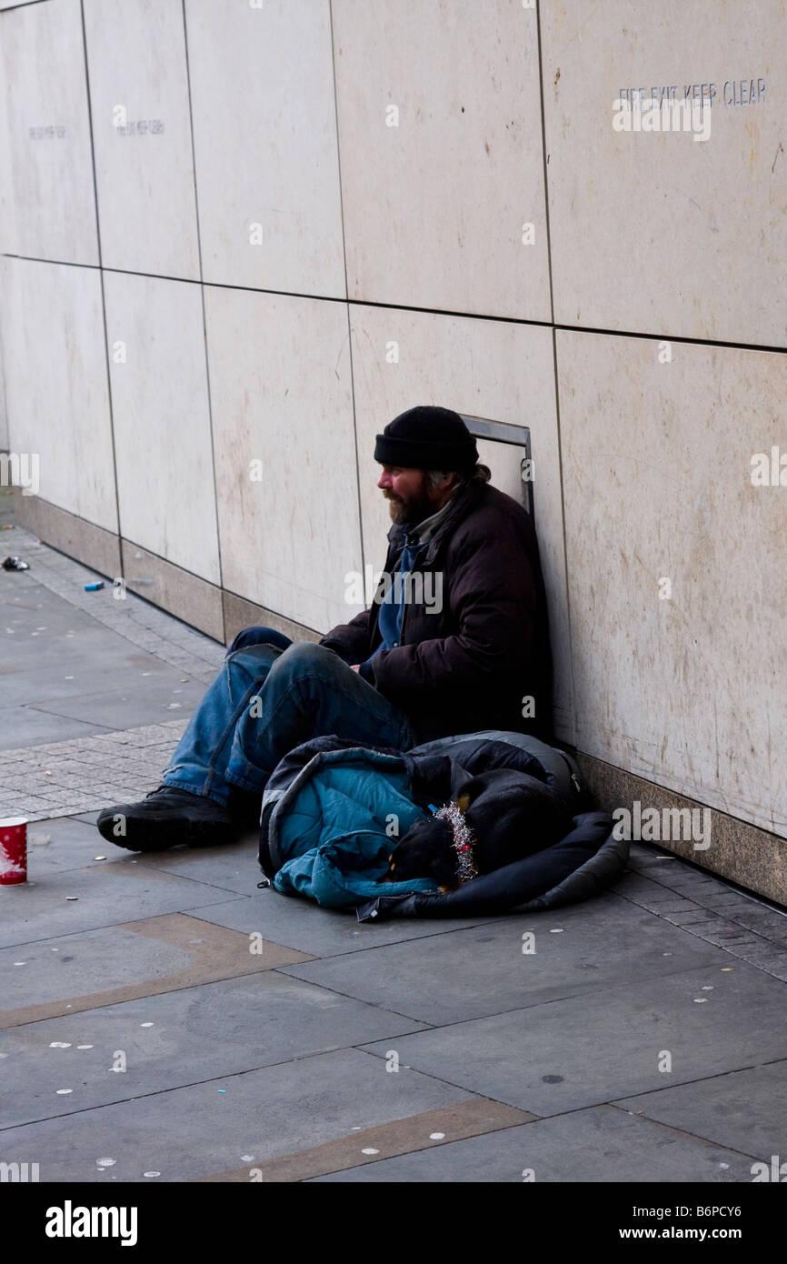 tramp begging with dog outside prestige shops - Stock Image
