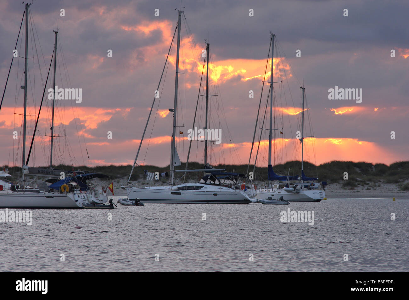 The sun rises among the clouds behind the ships anchored in the island of Espalmador, a small island in the Balearic Stock Photo