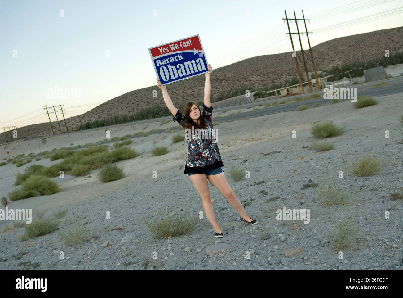 Barak Obama supporter holding up a 'Yes we can' election banner. - Stock Image