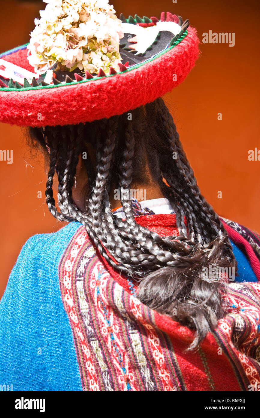 Back view of young Peruvian Quechuan woman girl wearing a traditional hat or Montera with plaits or pigtails, Chinchero, - Stock Image